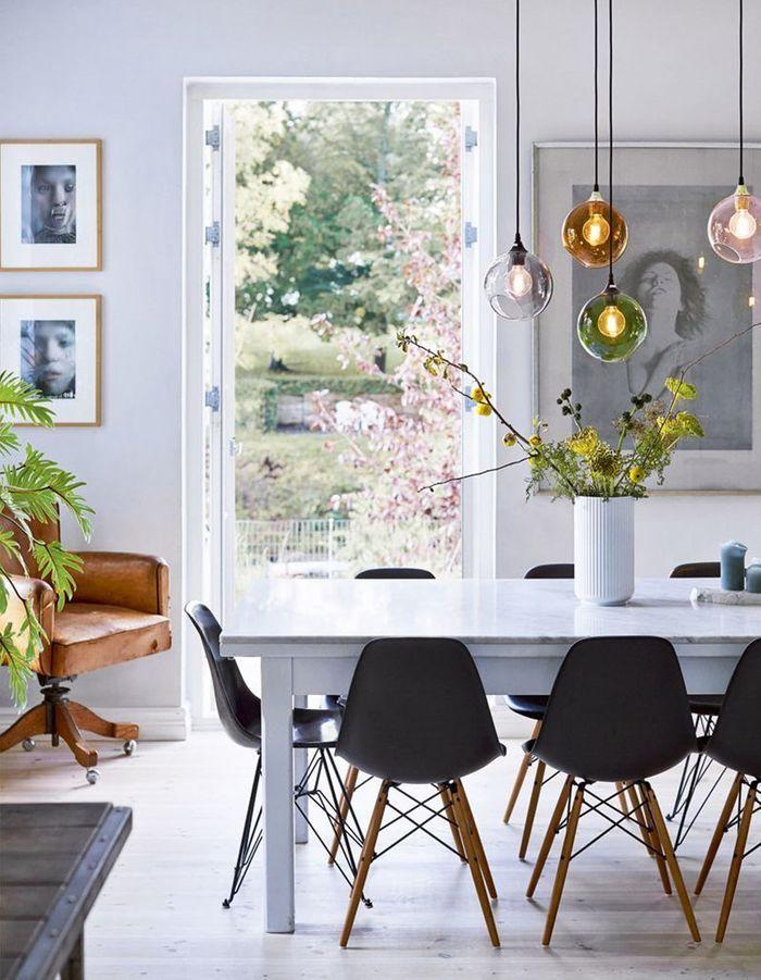 La chaise DSW noire autour d'une table à manger en marbre blanc