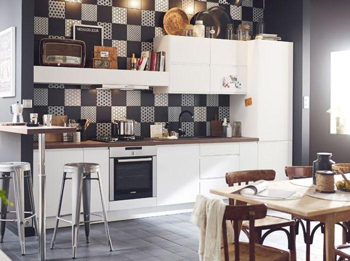 Une cuisine aux meubles blancs associés à une crédence et des murs noirs