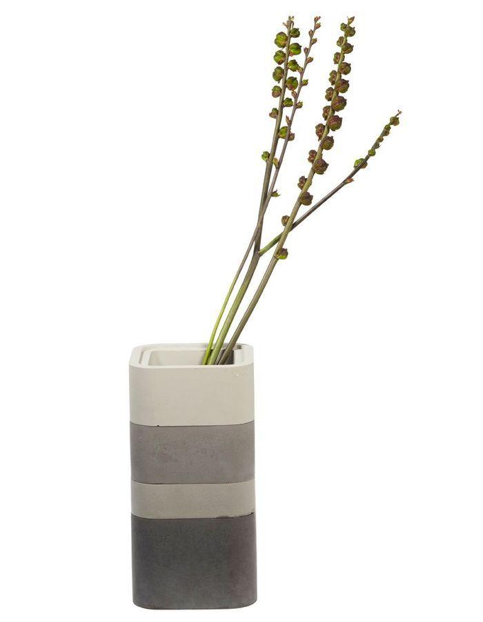 Un canapé gris accompagné d'un vase tout en camaïeu