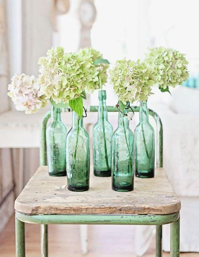 Des bouteilles en verres en guise de soliflores pour une déco de mariage pas chère